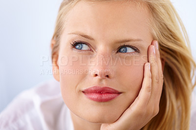 Buy stock photo Closeup shot of an attractive young woman leaning on her hand and looking sideways