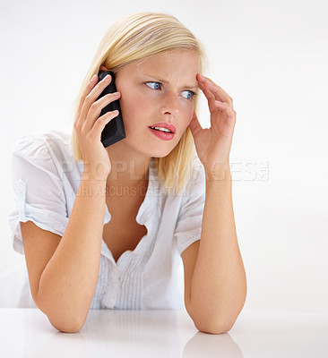 Buy stock photo Shot of an attractive woman looking worried while talking on her cellphone