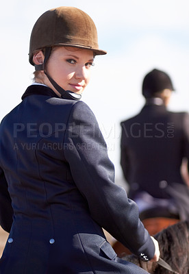 Buy stock photo Portrait of a young female rider mounted on her horse and looking over her shoulder at the camera