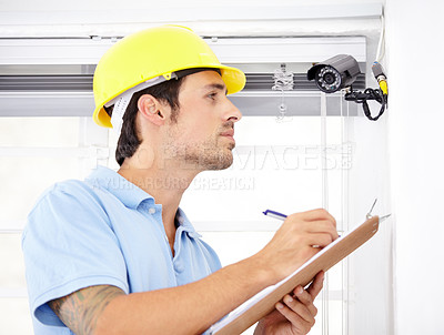 Buy stock photo Shot of a handsome young man    installing a security camera