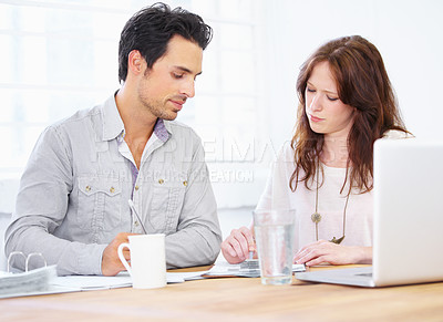 Buy stock photo Shot of a two young design professionals sitting together and going over some paperwork