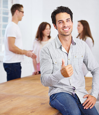 Buy stock photo Portrait of a young business professional giving the camera the thumbs up with coworkers talking in the background