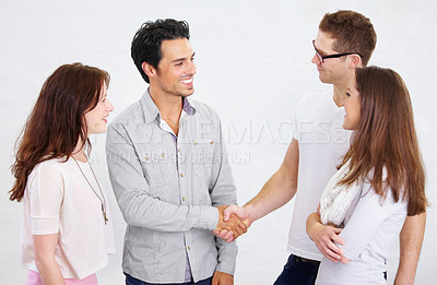 Buy stock photo Shot of a two young business professionals shaking hands while their coworkers look on