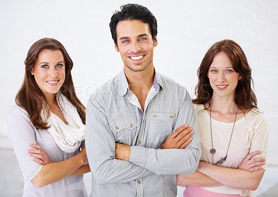 Buy stock photo Portrait of three positive-looking business professionals standing with their arms crossed
