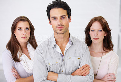 Buy stock photo Portrait of three serious-looking business professionals standing with their arms crossed