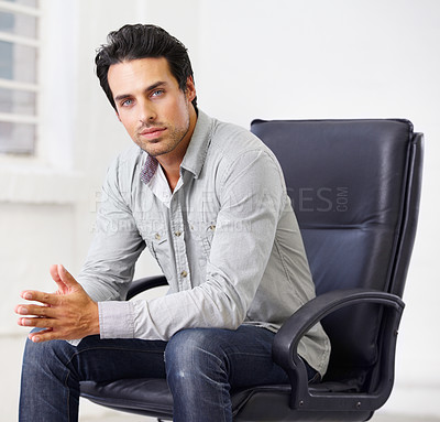 Buy stock photo Shot of a handsome young sitting in a chair