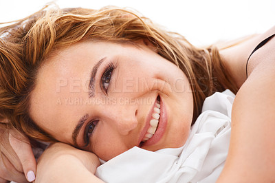 Buy stock photo A smiling woman who has just woken up lying in her bed