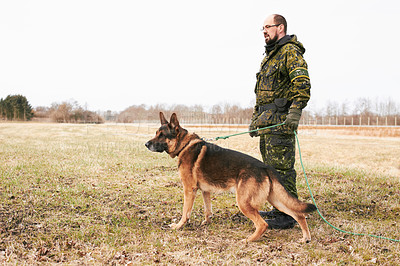 Buy stock photo A soldier standing in a field with his dog