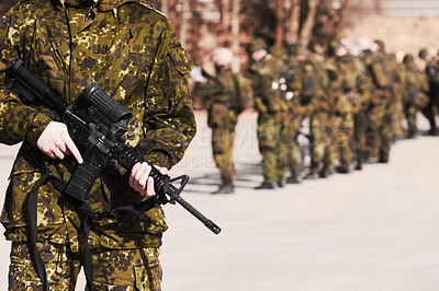 Buy stock photo A soldier standing with a rifle and his fellow soldiers in the background