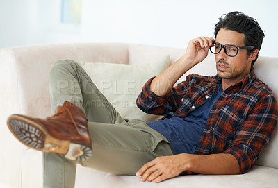 Buy stock photo A gorgeous fashionable young man lying on a sofa at home with legs crossed wearing spectacles