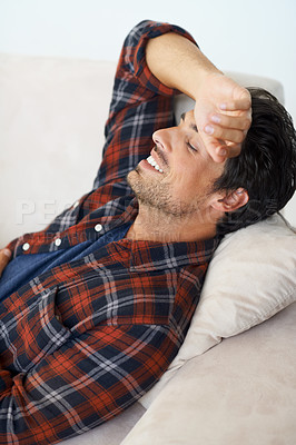 Buy stock photo A gorgeous young man lying down and smiling with his arm behind his head