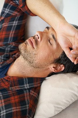 Buy stock photo A gorgeous young man lying down with his arm over his forehead and eyes closed