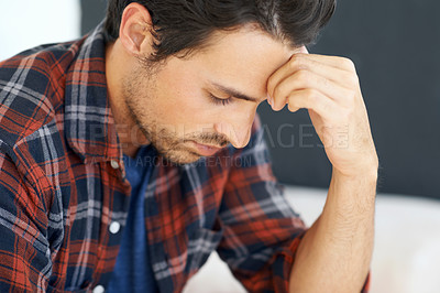 Buy stock photo Profile of a gorgeous young man sitting on a sofa and looking down with hand rested against his forehead and an expression of concern on his face