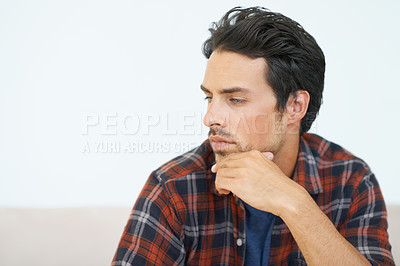 Buy stock photo A gorgeous young man sitting on a sofa with hand rested against his chin and an expression of contemplation on his face