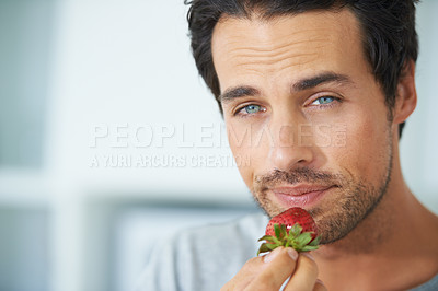 Buy stock photo A cropped portrait of a gorgeous young man holding a strawberry