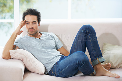 Buy stock photo A gorgeous young man lying on a sofa with his head resting on his hand