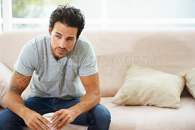 Buy stock photo A gorgeous young man sitting on a sofa and having a cup of coffee at home