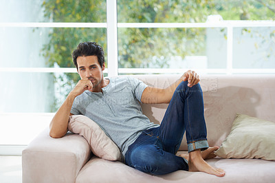 Buy stock photo A gorgeous young man lying on a sofa with his chin rested on his hand at home
