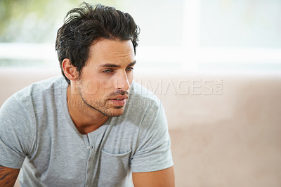 Buy stock photo A gorgeous young man sitting on a sofa at home