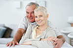 Senior couple sitting together at home smiling