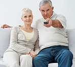 Charming senior couple sitting on a sofapointing remote control