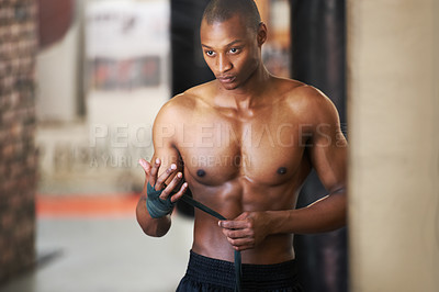 Buy stock photo An african american boxer taping up his hands at the gym