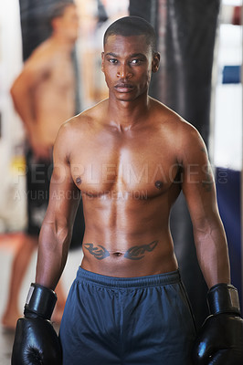 Buy stock photo A muscular young boxer looking at you with determination