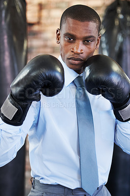 Buy stock photo A young african american boxer in a shirt and tie with his gloves up
