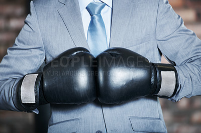 Buy stock photo A man in a suit punching his boxing gloves together