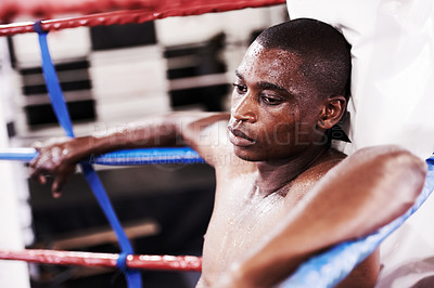 Buy stock photo An exhausted young boxer leaning against the ring after a trying round