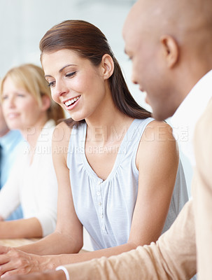 Buy stock photo A beautiful young businesswoman working with a colleague in the boardroom