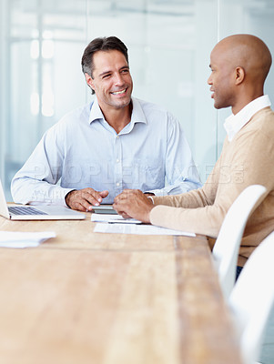 Buy stock photo Two businessman having a discussion in the boardroom at the office