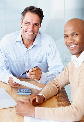 Buy stock photo Two handsome accountants working in the office together