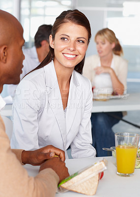 Buy stock photo A pretty young businesswoman talking to a colleague in the cafeteria