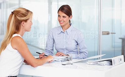 Buy stock photo Two businesswoman working on documents together in the office