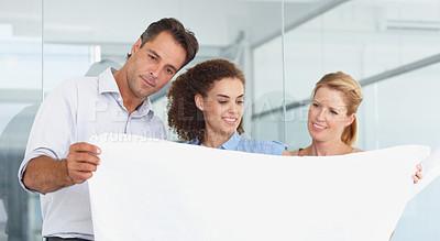 Buy stock photo Three architects looking at blueprints together