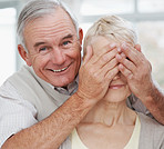 Closeup of an elderly man covering wife's eyes