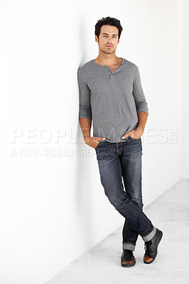 Buy stock photo Portrait of a handsome young man leaning against a wall with his hands in his pockets