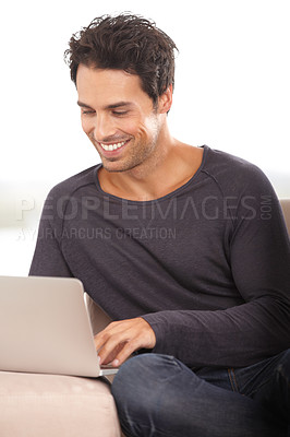 Buy stock photo A handsome young man surfing the web on his laptop at home