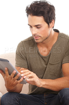 Buy stock photo A handsome young man using his digital tablet while sitting on the sofa at home
