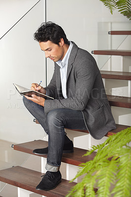 Buy stock photo A young businessman sitting on a staircase writing in his journal