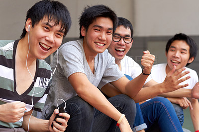 Buy stock photo Four young asian boys sitting in a row and cheering
