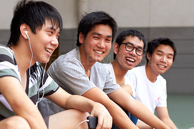 Buy stock photo Four young asian friends sitting in a row and smiling at the camera