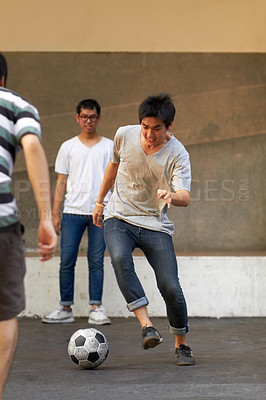 Buy stock photo Three asian teenagers playing soccer in the street