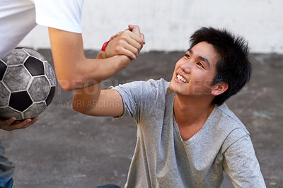 Buy stock photo Asian boy helping his friend up from the ground during a soccer game