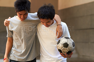 Buy stock photo Two asian boys walking with their arms around eachother holding a soccer ball
