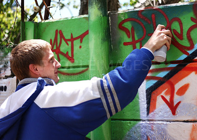 Buy stock photo Shot of a teenager spray painting a wall with graffiti