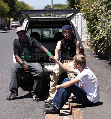 Buy stock photo Shot of three young men hanging out on the side of the road