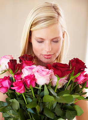 Buy stock photo A young woman smelling a bouquet of roses