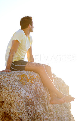 Buy stock photo Young man sitting on a rock with the sunset in the background